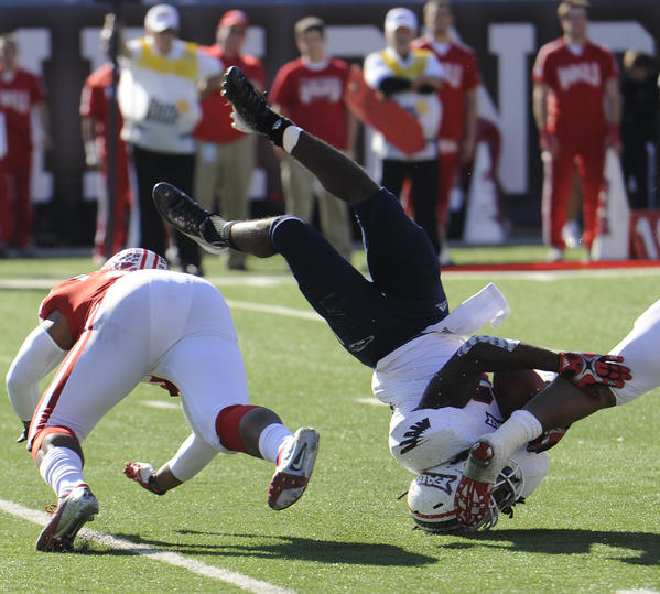 Florida Atlantic Owls running back Damian Fortner (22) is upended by Western Kentucky Hilltoppers linebacker Andrew Jackson (4) and Western Kentucky Hilltoppers defensive back Kiante Young (29) in the first half of an NCAA college football game in Bowling Green, Ky., Saturday,