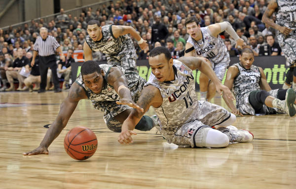 UConn guard Shabazz Napier (13) and Michigan State guard Branden Dawson dive for the ball Friday at Ramstein Air Base in Germany.