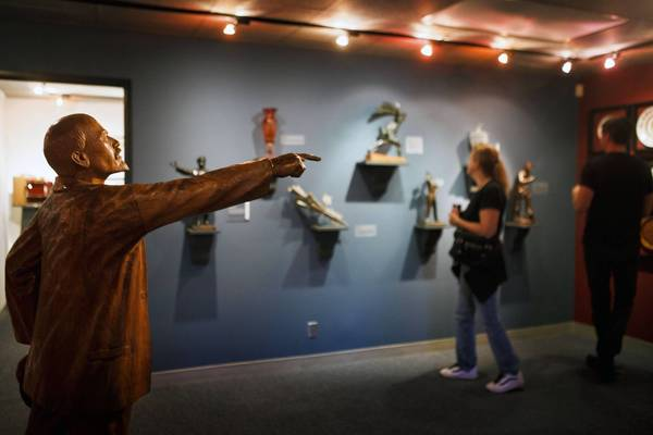 A carved wood sculpture of Vladimir Lenin by the ethnic Hungarian artist Csorvassy Istvan points at visitors to the Wende Museum of Cold War history.