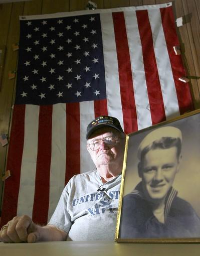 (abb) fl-korean-war-veterans-110712a - Korean War veteran Paul Flanagan is shown with a photo of himself in his early twenties when he was enlisted in the Navy. This at the American Legion Post in Oakland Park on Wednesday, Nov. 7, 2012. Amy Beth Bennett, Sun Sentinel