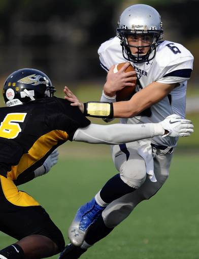 Manchester Valley quarterback Dominick Frank, right, tries to elude Reginald Lewis defender Nay Sutton during the first half of a Class 1A South regional semifinal football game Saturday, Nov. 10, at Baltimore Polytechnic Institute.