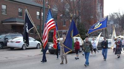 A color guard made up of military veterans and supporters walks north along Howard Street today, Sunday, during Petoskey's Veterans Day parade.