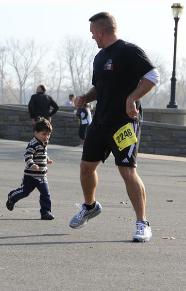 Dave Williams, a veteran of the U.S. Marine Corps, runs with his son Roge, 2, prior to the start of the Freedom Run 5K at Riverside Park in Hartford Sunday.