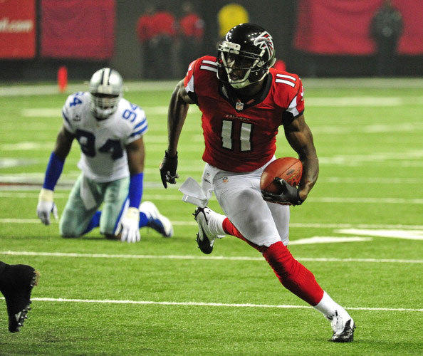 Julio Jones #11 of the Atlanta Falcons runs with a catch against DeMarcus Ware #94 of the Dallas Cowboys at the Georgia Dome on November 4, 2012 in Atlanta, Georgia.