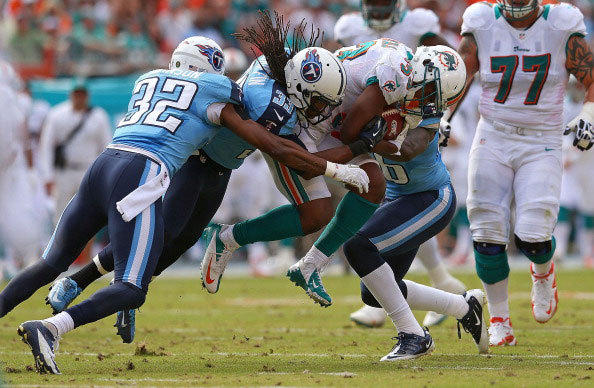 Daniel Thomas #33 of the Miami Dolphins is tackeled by Michael Griffin #33 of the Tennessee Titans during a game at Sun Life Stadium on November 11, 2012 in Miami Gardens, Florida.
