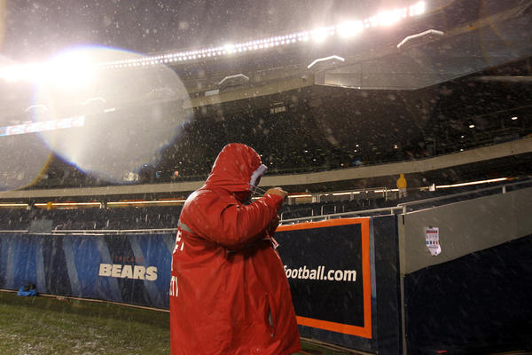 A security guard tightens his hood as rain falls before Chicago Bears play Houston Texans in NFL game at Soldier Field on Sunday. Scott Strazzante, Chicago Tribune