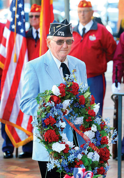 Pat Patterson, a U.S. Army veteran from the Korean War, places a wreath on behalf of the Joint Veterans Council Sunday at the Washington County Courthouse.