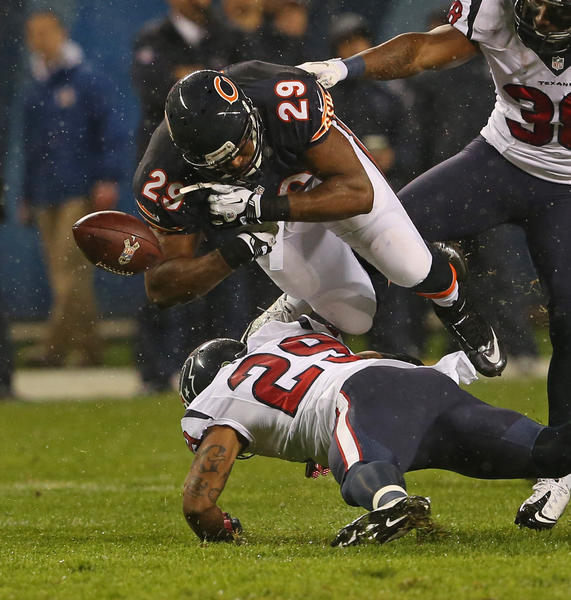 Bears running back Michael Bush fumbles while going over Texans strong safety Glover Quin during the first half.