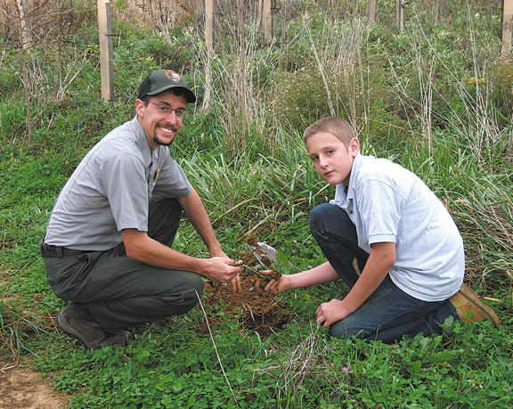 Ranger Andrew Landsman of Antietam National Battlefield plants a seedling with Antietam Academy student Brian Rowland.