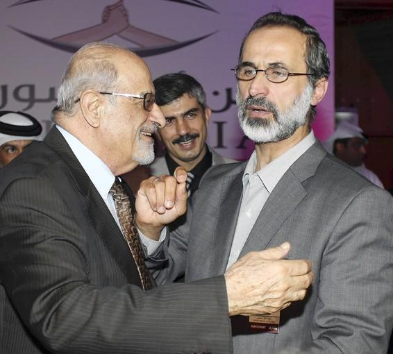Syrian human rights activist Haytham Maleh, left, congratulates Moaz Khatib in Doha, Qatar, after he was elected to lead the new Syrian opposition alliance.