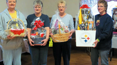 Linda Sesack, Cindy Adomnik, Judy Blough and Betty Lou Rapsky, put the final touches on the basket party/spaghetti dinner they coordinated to help Sharon and Steve Seraski of Central City, who are both ill and unable to work.