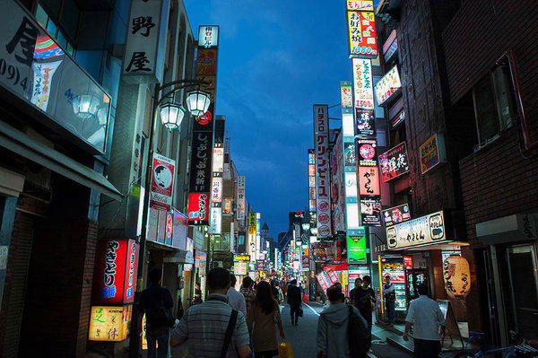 People walk along a street as store signs light up at night in Tokyo.