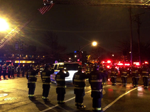 Firefighters salute a procession of vehicles arriving at the Cook County medical examiner's office after a fellow firefighter died of cardiac arrest after fighting a small fire on Chicago's South Side.
