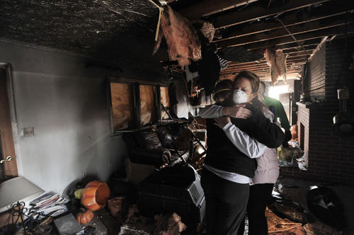 Kerri Bandelin hugs Becky Shire, Hunt Valley, her sister-in-law, inside her burned home.