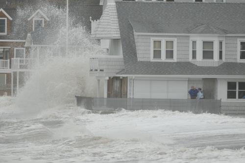 Bob Post and his daughter Lauren check out the heavy storm surge hitting Bayview Beach in Milford from a friend's oceanfront home Monday afternoon.