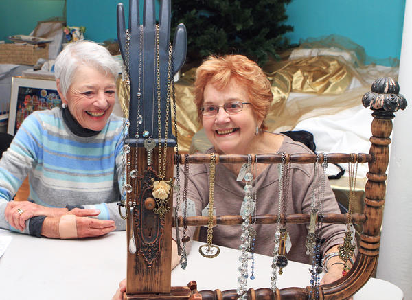 Wally Klein of Charlevoix (left) and Rhea Murray of Petoskey marvel at the creativity in  the unique display rack and found-art jewelry submitted by Indy Bacon of Hartland (not shown), as they check in items recently for the Holiday Art Bazaar at Crooked Tree Art Center, Petoskey.