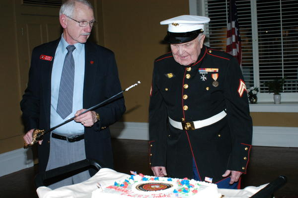 Commandant Mike Griffin cuts the Marine Corps birthday cake and Corporal Kenneth Staley receives the first piece of cake Saturday at the 237th Marine Corps birthday celebration at the Perry Hotel in Petoskey. Staley, 90, the oldest Marine at the celebration, served in World War II and in China.