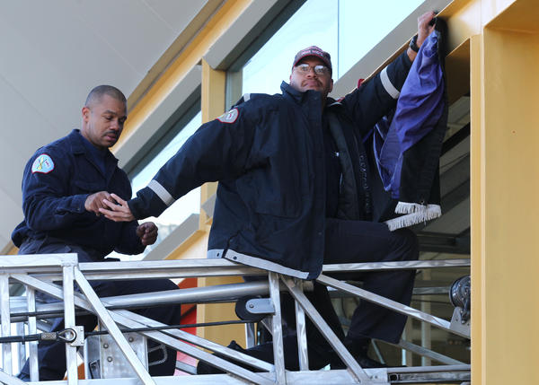 Firefighters Lewis Williams, right, and Dave Beason, left put up bunting outside Engine Company No. 121 at 1700 West 95th Street in Chicago on Monday. Firefighter Walter Patmon Jr., 61, an 18-year veteran Chicago firefighter, died late Sunday after going into cardiac arrest within hours of responding to a blaze on the city's South Side, officials said. (Nancy Stone, Chicago Tribune)