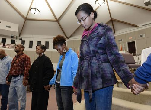 Greater Shiloh Church member Melanie Tawwab, 14, of Wilson (right) listens as minister Roxanne Robinson leads a prayer to help the needy, before members of the congregation depart Easton to deliver donated clothing food and other supplies to Far Rockaway, New York on Monday. F