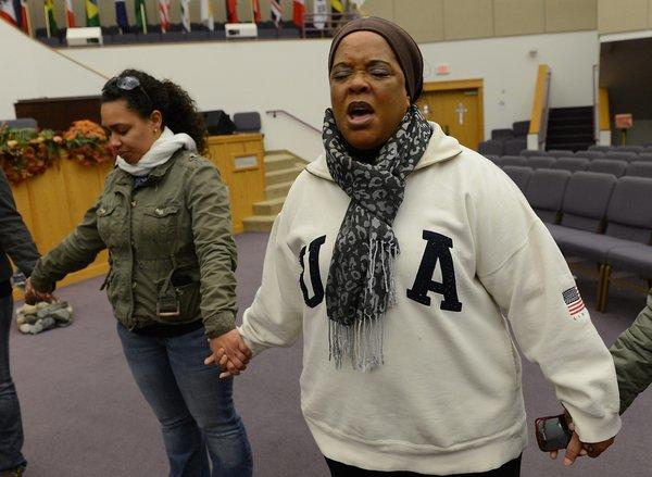 Greater Shiloh Church minister Roxanne Robinson (right) leads a prayer to help the needy, before members of the Easton congregation leave to deliver donated clothing food and other supplies to Far Rockaway, New York on Monday. Far Rockaway was among the hardest hit communities in the aftermath of Hurricane Sandy.