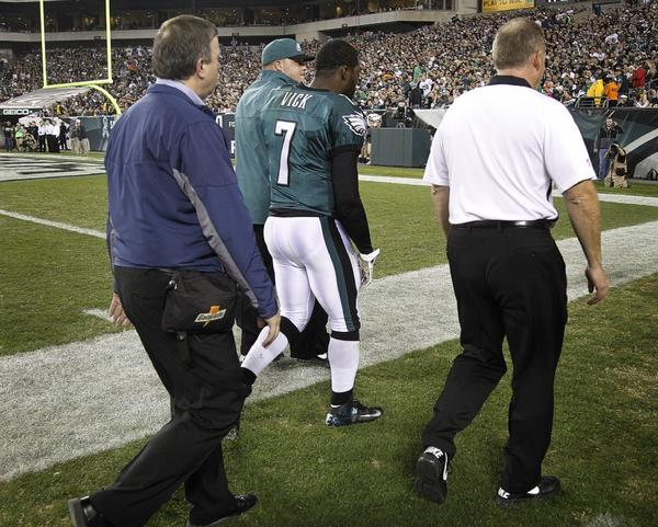 Philadelphia Eagles quarterback Michael Vick walks off the field after being injured against Dallas.