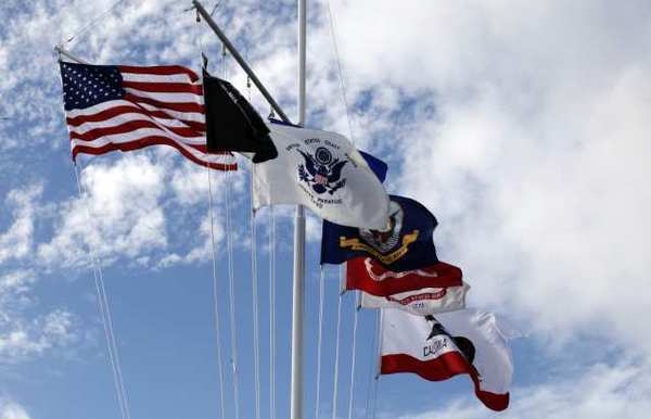 Flags denoting all branches of the US military services, including a POW-MIA flag are flown during a Veterans Day tribute.