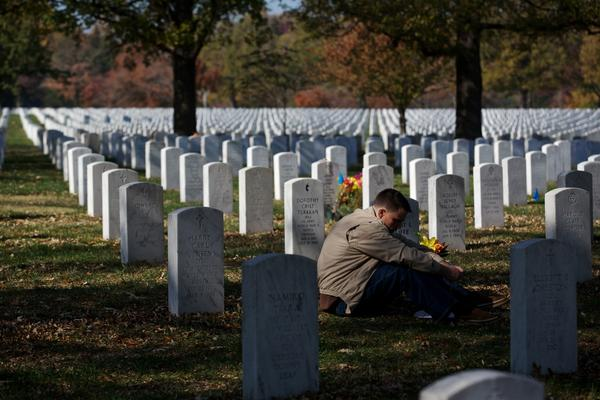 Capt. Jeff Cliffe, with the U.S. Marine Corps, sits next to the grave of his grandfather and grandmother on Veterans Day at Arlington National Cemetery.