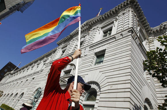 Ken Pierce of Equality Action Now, waves a rainbow flag outside a San Francisco courthouse in Dec. 2011.
