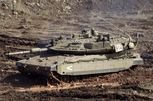 An Israeli tank in a firing position Monday in the Israeli-controlled Golan Heights overlooking the Syrian village of Bariqa. The Israeli military says Syrian mobile artillery was hit after Israel responded to apparently stray mortar fire from its neighbor.