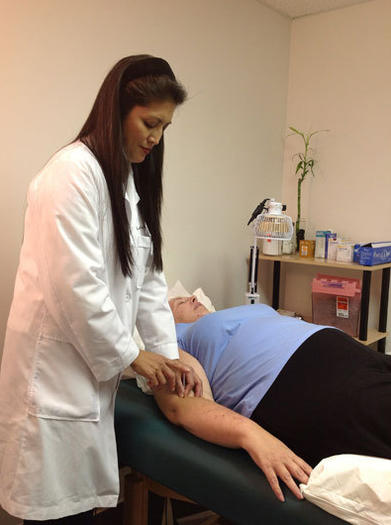Dr. Lorenu Wu, president of the Illinois Chapter of the American Academy of Medical Acupuncture, inserts acupuncture needles into one of her patients. Wu is a medical doctor with a family practice in La Grange.