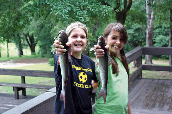 "Two participants show off fish they caught during one of the Wildlife Foundation of Florida's (WFF) programs. On Nov. 17 the foundation will host the inaugural ""Florida BlueGreen"" at ""Alligator"" Ron Bergeron's ranch located in Weston. Event proceeds from the Florida cracker-style cowboy gala will benefit the foundation's Florida Youth Conservation Centers Network and several other youth and conservation initiatives in Florida."