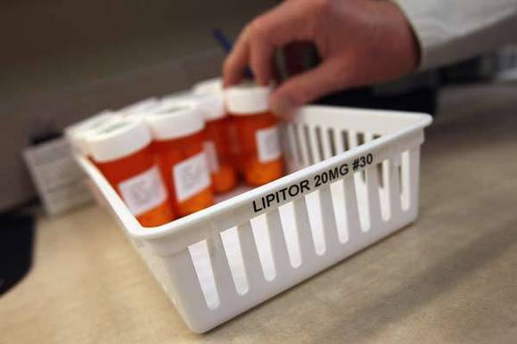 A pharmacist takes a bottle of cholesterol-reduction medication while filling prescriptions at a community health center