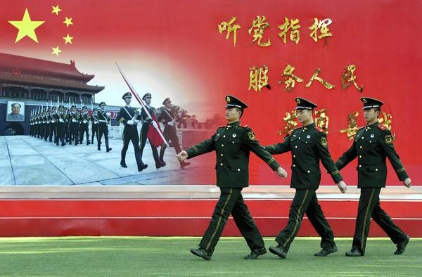 "Chinese paramilitary police march past a sign that reads, ""Serve the party and the people,"" near the Great Hall of the People in Beijing, where the Communist Party is holding its 18th congress."