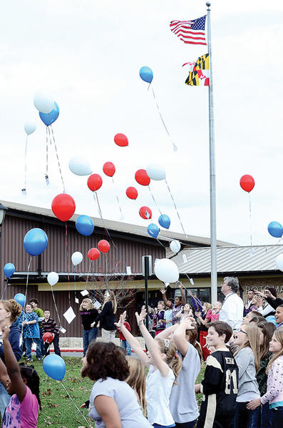 Students and staff at Potomac Heights Elementary School release red, white and blue balloons Monday afternoon during a Veterans Day celebration.