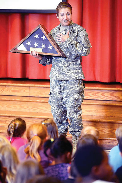 U.S. Army Maj. Laura Peters presents a U.S. flag Monday to Potomac Heights Elementary School during a Veterans Day celebration. The flag was in memory of the late U.S. Army 1st Lt. Ashley White-Stumpf, who died in service on Oct. 22, 2011.