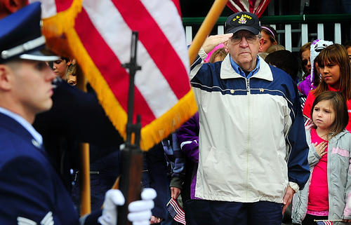 U.S. Army veteran Charles Lumm and students from Sharpsburg Elementary School, including fourth-grader Cheyanne Thacker, salute Monday during a Veterans Day program on the town's square.