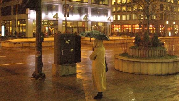 A woman uses an umbrella to keep out the snow Monday night on Michigan Avenue.