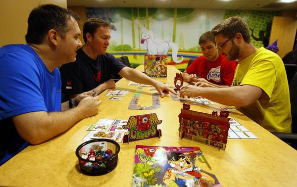 From left: Kyle Heuer, Matt Hyra, Will Brinkman and Phil Cape play Hot Rod Creeps, a card-driven racing game, at Cryptozoic Entertainment in Irvine, California.