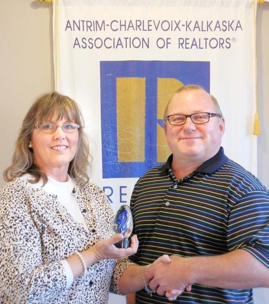 Lynn Robinson (left), president of the Antrim Charlevoix Kalkaska Association of Realtors, is presented with the 2012 Realtor of the Year award byGreg Bryan,past-president and current secretary/treasurer of the association.