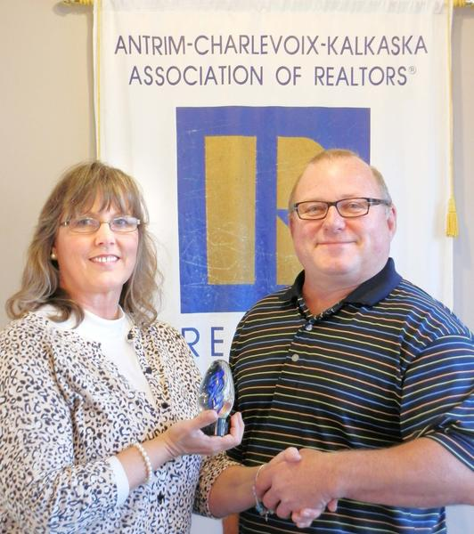 Lynn Robinson (left), president of the Antrim Charlevoix Kalkaska Association of Realtors, is presented with the 2012 Realtor of the Year award by Greg Bryan, past-president and current secretary/treasurer of the association.