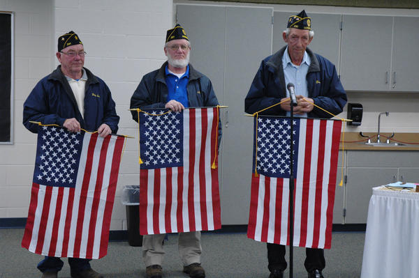 John Cupps Sr. (from left), Colin McFarland and David JOhnston, American Legion Post 281 members, display the flags they have donated to Harbor Springs Public Schools.