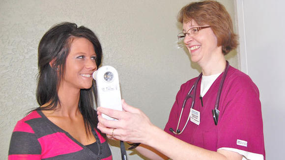 Tendercare's Jessica Johnson (l), director of sales and marketing, and Leslie Miller, respiratory therapist, demonstrate the simple little instrument used in spirometry testing that can detect COPD before symptoms become severe.