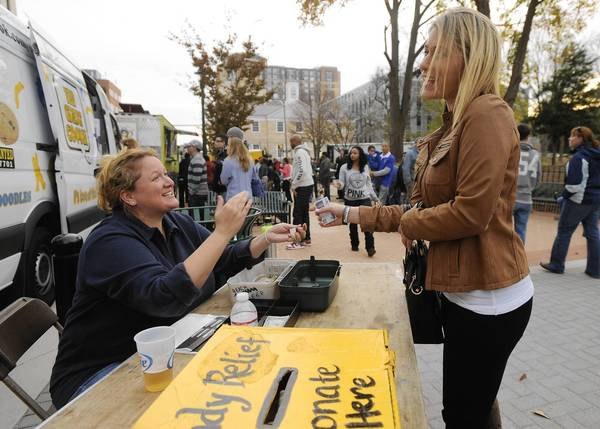 Jae Abate, of Ruxton, sells a wrist band to Robyn Cohen, of West Towson, during the food truck rally Saturday in Towson. Attendees were encouraged to bring relief items that will be sent straight to those affected by Superstorm Sandy.