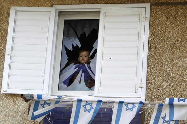 A baby is seen at a broken window after a rocket fired by Palestinian militants in Gaza hit a house in the southern town of Netivot. The Palestinian rocket fired from the Gaza Strip struck the house in southern Israel on Monday, causing damage but no injuries, and Israeli officials quickly warned of a tough response to the latest surge in violence.