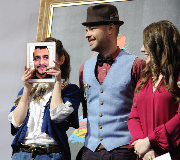 "Maria Barracuda, left, of the Mexican pop group Jotdog hides behind a live iPad image of her Jotdog partner Jorge ""La Chiquis"" Amaro at the 13th annual Latin Grammy Awards nominations press conference in L.A. last September. With her are Jesse, center, and Joy Huerta of the Mexican pop duo Jesse & Joy."
