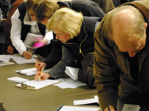 Winnetka residents sign petitions after the Nov. 12 Caucus Town Meeting to help put the slated candidates on the upcoming spring election ballot.