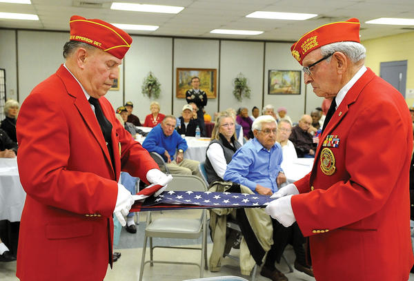 Paul Blackwell, left, and Frank Farmer, members of the Marine Corps League¿s Harold G. Epperson Medal of Honor Detachment No. 1113, demonstrate the proper way to fold an American flag Monday while fellow Marine Don Rose explains the meaning of each fold during the Generations Center Veterans Day program, top photo. Clark County Judge Executive Henry Branham, right, presents a certificate to Coleman Ginter, third from left, who served in the U.S. Army, above right. Others receiving certificates included, from left, Dewayne Roller, Willard Ritchie, and Bill Blakeman. Eighteen veterans were recognized and presented certificates. St. Agatha Academy student Maddie Goeing sings ¿America¿ along with the rest of the students during the school¿s Veterans Day program, left photo. Veteran Clair Hunter was the guest speaker during the program, right photo. He spoke of some of his experiences during his 28 years of active duty.