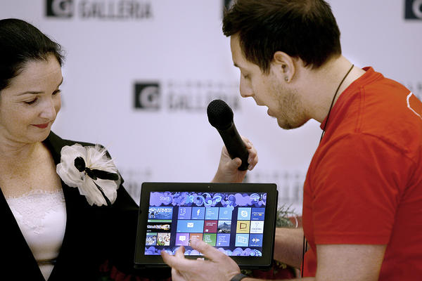 As Glendale Galleria's senior marketing manager Shoshana Puccia holds the microphone, left, the the Galleria's Microsoft Store's Douglas Carlson shows the new Surface tablet ($499-$699) during holiday press conference at the Glendale indoor mall on Tuesday, Nov. 13, 2012.  The large hands play sounds from the same-title movie and cost $24.50.