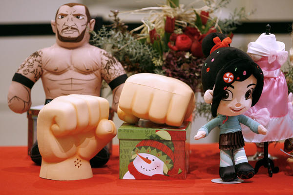 A pair of Wreck-It Ralph Smash Hands from the Disney Store, front left, along with a Vanellope Von Schweetz doll, front right, and  Target's WWE Brawlin Buddies Randy Orton ($24.99), where shown during holiday press conference at the Glendale indoor mall on Tuesday, Nov. 13, 2012.  The large hands play sounds from the same-title movie and cost $24.50 but the Vanellope had no price.