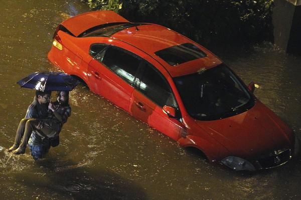 A man carries a woman past a car partially submerged in flood waters following a heavy rain in Beijing back in July.